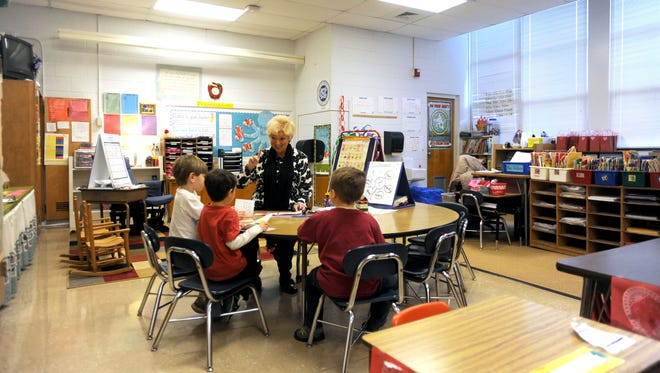 Woodfin Elementary School teacher Suzie Robinson-Park, center, works with kindergarden students during a reading exercise at the school in February.
