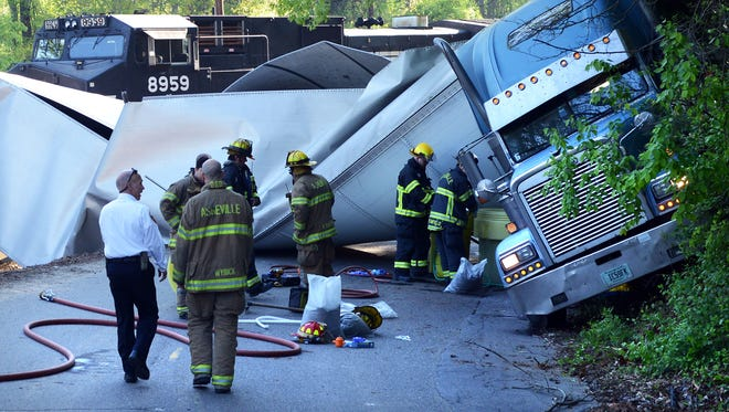 Members of the Asheville Fire Department remove diesel fuel from a tractor-trailer that collided with a train Thursday morning at a crossing on Glendale Ave. The crash occurred before 6 a.m.