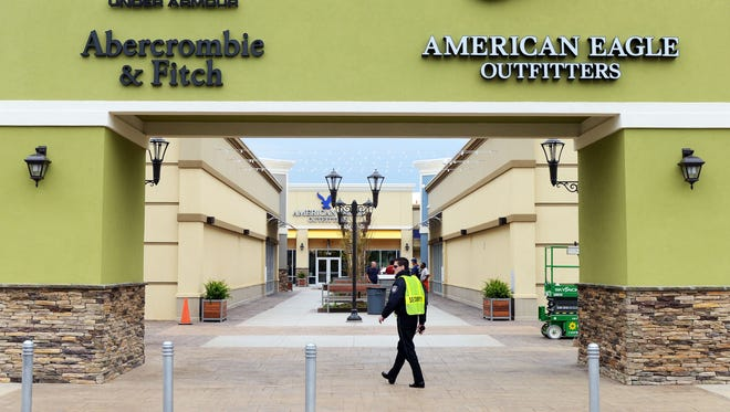 A security guard keeps watch at an entrance to the new Asheville Outlets mall. Three more stores will be opening at the Asheville Outlets next week.