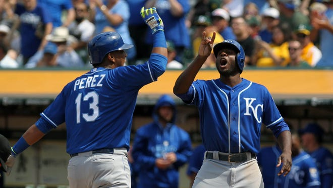 Kansas City Royals catcher Salvador Perez (13) and center fielder Lorenzo Cain (6) celebrate after Perez hit a two run home run in the eighth inning of their MLB baseball game with the Oakland Athletics at O.co Coliseum.