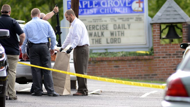 Investigators bag guns into evidence in the Maple Grove Baptist Church off Stamey Cove Road Wednesday.