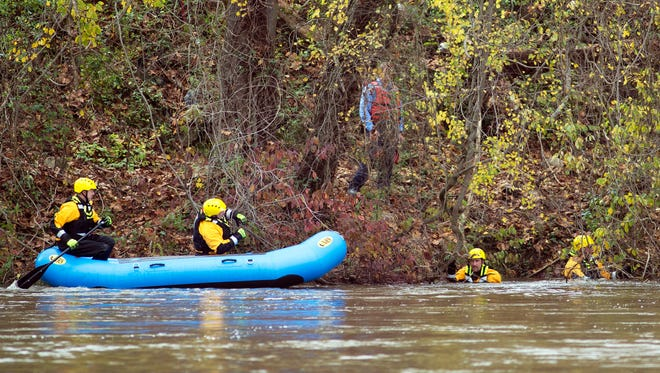 Members of the Asheville Fire Department Rescue 3, Squad 1 search the west bank of the French Broad River in downtown Tuesday searching for clues in the disappearance of Alexandra King, 22, and Tatianna Diz, 20, who have been missing for a week.
