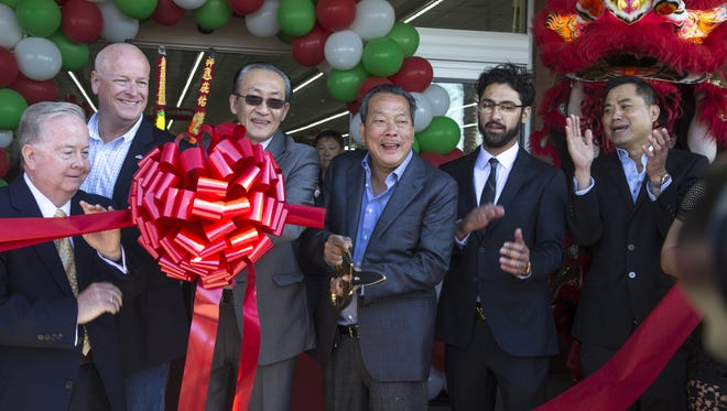 Co-owners Peter Quach (center) and Jimmy Lai (3rd from left) cut the ribbon during the AZ International Marketplace grand opening, April 20, 2016, in Mesa.