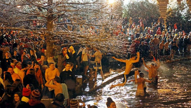 In this 2013 file photo, Ohio State University students gather around Mirror Lake on the campus in Columbus.