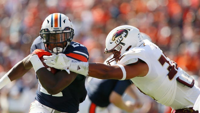 Auburn Tigers running back Kerryon Johnson (21) is tackled by ULM linebacker Chase Day (32) during the first quarter at Jordan Hare Stadium.