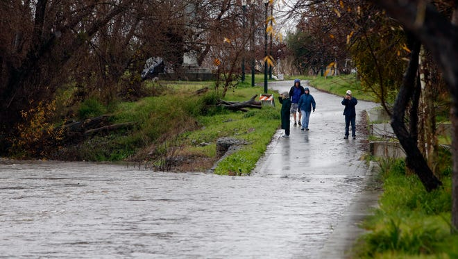 Spectators wander down the Guadalupe River Trail to watch the swollen river as it flows during a storm Jan. 8, 2017, in San Jose.