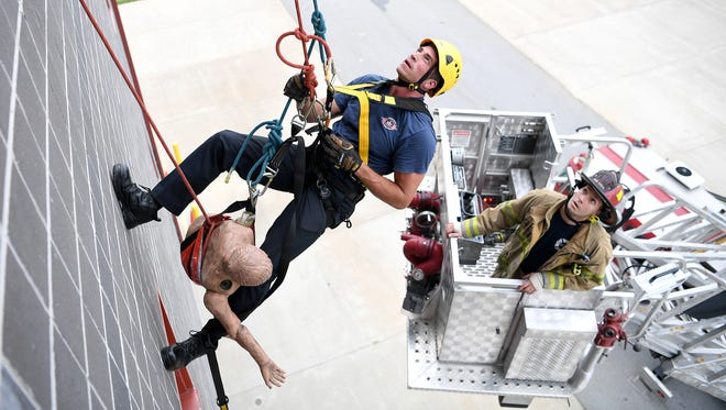 Asheville Fire Department recruit Jeremy McDonnell, left, rappels down a wall to retrieve a dummy hanging from a window as AFD Lt. Dale Wyrick, watches from a ladder truck during the Asheville Fire Department's graduation exercises of recruits at the Buncombe County Emergency Services Training Facility on Thursday, Aug. 10, 2017.