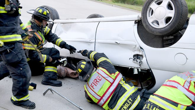 Marco Liubenov, left, and Chad Hensley, right, work together to rescue a dummy trapped under a car that flipped down an embankment during the Asheville Fire Department's graduation exercises of recruits at the Buncombe County Emergency Services Training Facility on Thursday, Aug. 10, 2017.