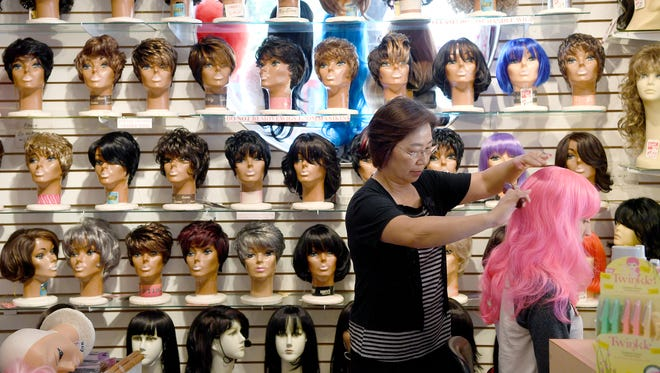 Sandy Kanupp brushes a pink wig on Kaitlyn Merrels' head at Kim's Wig Center downtown on Monday, Oct. 16, 2017.