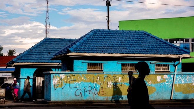 "People walk past a wall with a graffiti reading ""We want garwe (crocodile in Shona language)"" referring to sacked vice president Emmerson Mnangagwa, on Nov. 15, 2017 in Harare, Zimbabwe."