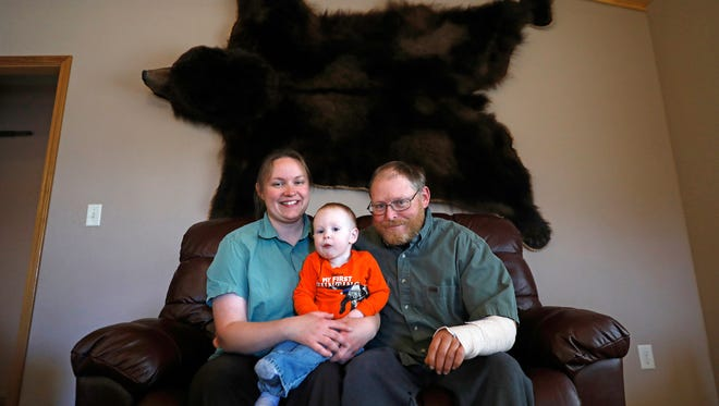 In this photo taken Nov. 16, 2017, Genevieve, left, Asher, 1, center, and Jonathan Sheets, right, sit for a portrait beneath an Alaskan brown bear pelt Genevieve bagged in 2011 in their home in Powell, Wyo.