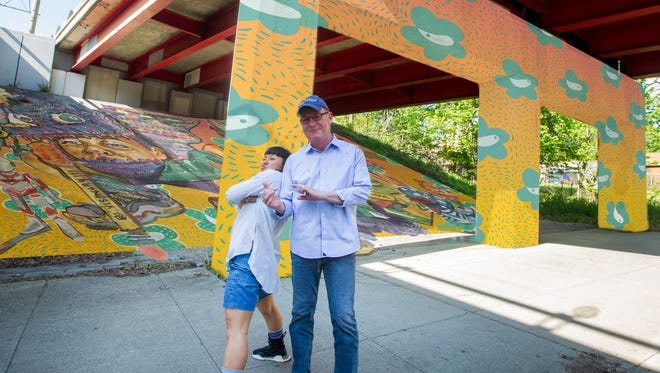 Artist Risa Tochigi, aka Boogie, is shown with Poughkeepsie Major Rob Rolison at the Route 9 underpass on Main Street with a mock-up design of her work which has been selected as the mural forthe Poughkeepsie Gateway Project.