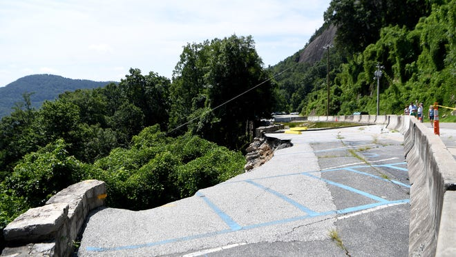 A collapsed retaining wall in the upper parking lot is barricaded from visitors as they walk from the shuttle bus toward the gift shop at Chimney Rock State Park on Friday, June 29, 2018. The wall collapsed due to rain at the end of May.