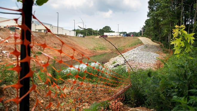 Orange plastic fencing divides a construction site, left, from wetlands, right, that it borders in Cookeville, Tenn., Tuesday, July 17, 2018.