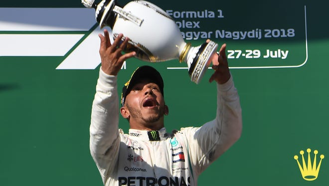 Lewis Hamilton celebrates with the trophy after winning the Hungarian Grand Prix Sunday.