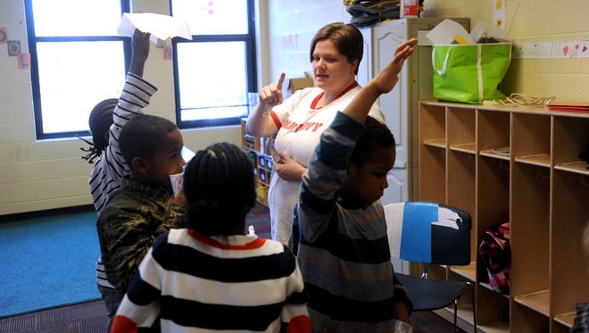 Kim Akbar, center, works with a group of kids during a spelling exercise Wednesday at the YWCA off French Broad Avenue. Akbar has been a paid teacher at the nonprofit for over a year.