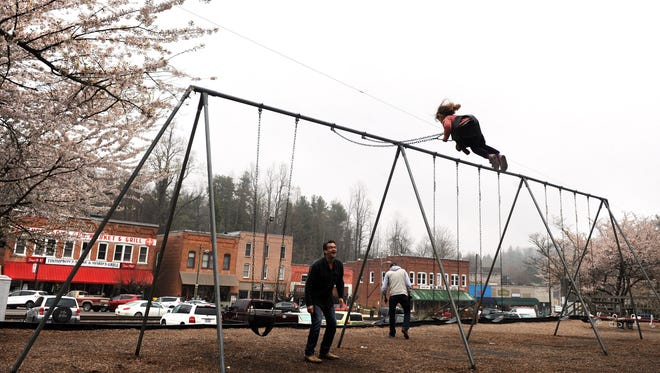 Donnie Fowler and his 3-year-old daughter Cleo play on a swing set in downtown Saluda on Thursday. The city had no brand and no outward identity to share with the world until a few weeks ago.