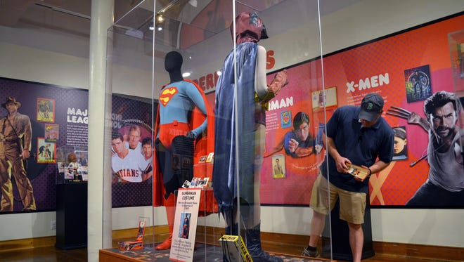 """A visitor looks at the original Batman costume that Adam West wore in the 1960s television show, on display next to a Superman costume worn by Christopher Reeve in """"Superman IV,"""" at the Louisville Slugger Museum."""