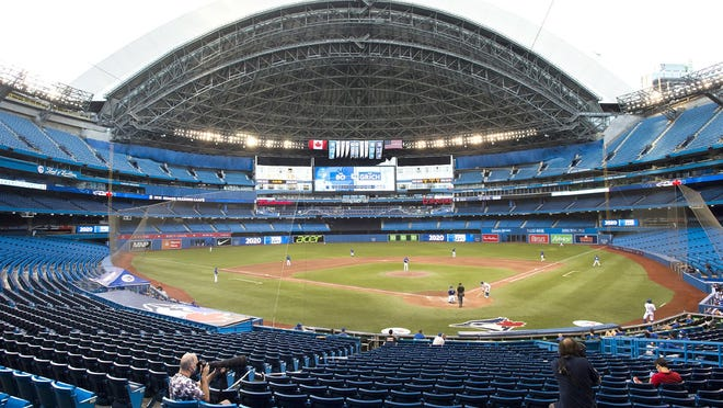 Photographers cover a July 17 Blue Jays game in an empty stadium during fourth-inning intrasquad action in Toronto.