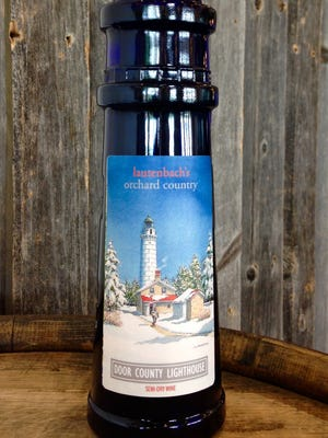 """A painting of Cana Island Lighthouse by Charles """"Chick Peterson is featured on the label of this year's Door County Lighthouse wine form Lautenbach's Orchard Country Winery in Fish Creek."""