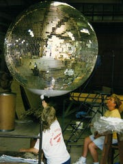 Yolanda Baker (left) and Nora Davis (right) work on a 4-foot disco ball at Omega National Products.