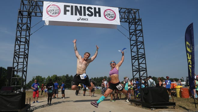 Camren Von Davis and Annabel Lukins jump at the end of the Roo Run at the Bonnaroo Music and Arts Festival 2018 on early Saturday morning, June 9, 2018
