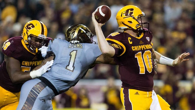 Central Michigan quarterback Cooper Rush (10) attempts to throw as Western Michigan defensive end Keion Adams (1) gets a hand on him during the first half.