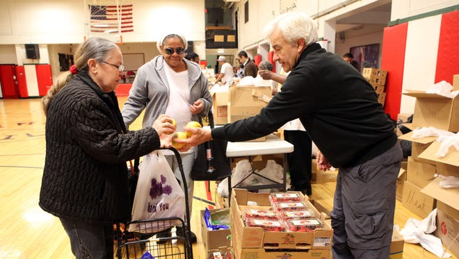 Volunteer Steve Pucillo hands out fruit during a mobile site set up by Steppin' Up Yonkers' Angel Food Pantry last year. Steppin' Up Yonkers is one of the three groups the Volunteer Hunger Relief Corps will be working with to help make strides to end hunger in Westchester and Rockland counties.