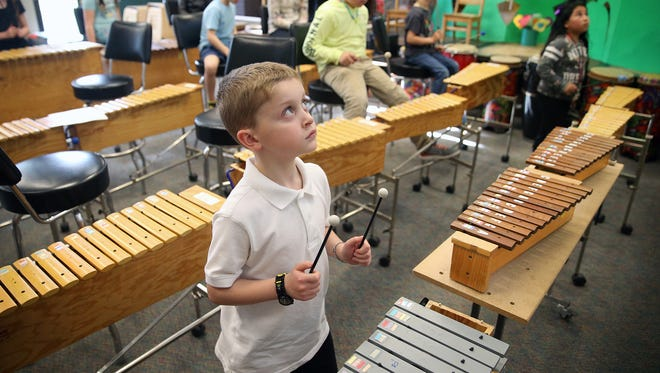 Sean Rivers, a second-grader at View Ridge Elementary Arts Academy, plays the soprano metallophone during the school's arts and literacy night on Tuesday.