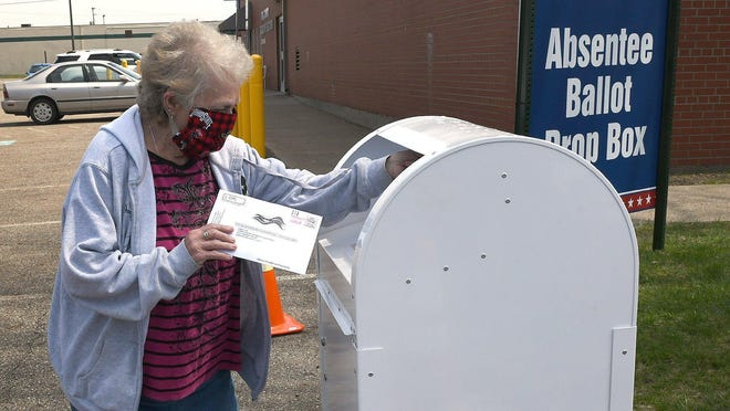 Fern Gosnell of Canton, Ohio, puts her absentee ballott into the drop box outside the Stark County Board of Elections, on April 24, 2020.