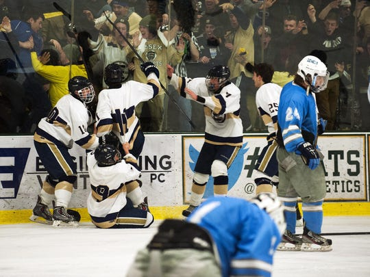 Essex celebrates its triple-overtime victory in the Division I boys hockey state championship against the South Burlington Rebels at Gutterson Fieldhouse on March 9.