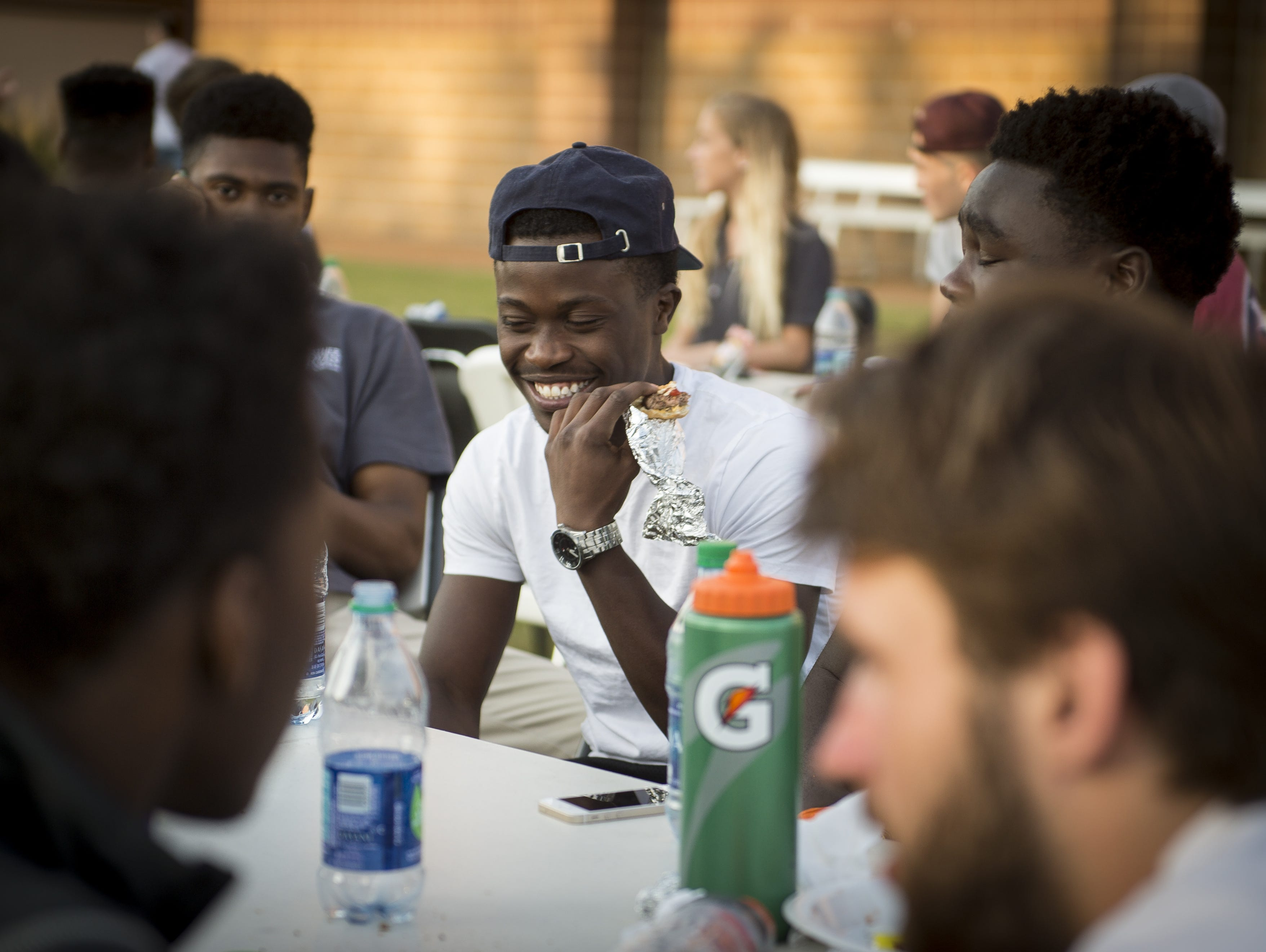 Father Ryan's Elton Nkwembe, center, jokes with friends during a cookout Friday.
