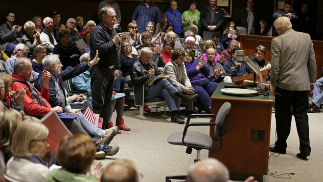 U.S. Rep. Glenn Grothman, right, listens to Jerry Scribner ask if the Republican congressman would make sure that any tax cuts do not increase the deficit. The town hall took place Sunday night at a packed room at Neenah's City Hall.