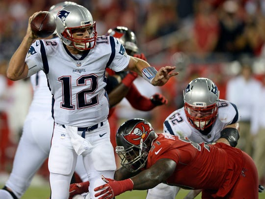 New England Patriots quarterback Tom Brady (12) looks to throws a pass as he is pressured by Tampa Bay Buccaneers defensive end Robert Ayers (91) during the first half of an NFL football game, Thursday, Oct. 5, 2017, in Tampa, Fla. (AP Photo/Jason Behnken)