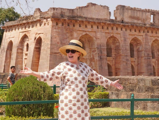 Hillary Clinton gestures outside the remains of the