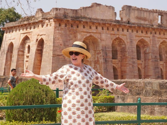 Hillary Clinton gestures outside the remains of the Hindola Mahal monument, part of an abandoned royal palace complex, while on a personal trip to the ancient city of Mandu in India's Madhya Pradesh state.