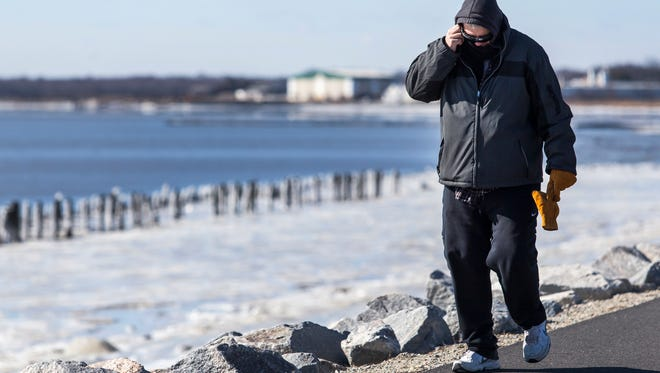 Jerry Twaddell walks along the frozen shoreline of Battery Park in New Castle on Sunday afternoon. Chilly conditions are expected to continue Monday.