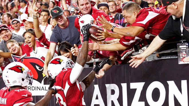 Cardinals running back Chris Johnson celebrates by giving a ball to a fan after scoring a touchdown against the Baltimore Ravens in the first half on Oct. 26, 2015 in Glendale, Ariz.