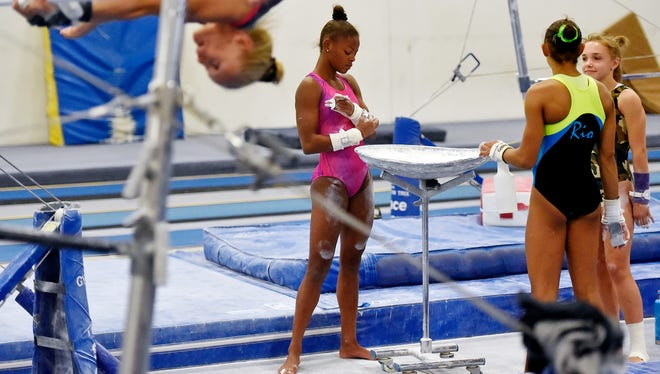 Trinity Thomas chalks up while practicing her uneven bars routine Thursday, Aug. 31, 2017, at Prestige Gymnastics in Lancaster County. Sisters Trinity Thomas, 16, and Tesia Thomas, 14, are different athletes in their own right, but each excels in her chosen discipline. Trinity Thomas is a gymnast on the U.S. senior national team who will attend Team USA's selection camp this month for a shot at a place on the squad for the world championships. Tesia Thomas is a standout three-season athlete for West York, where she plays volleyball, swims and is on the track and field team.