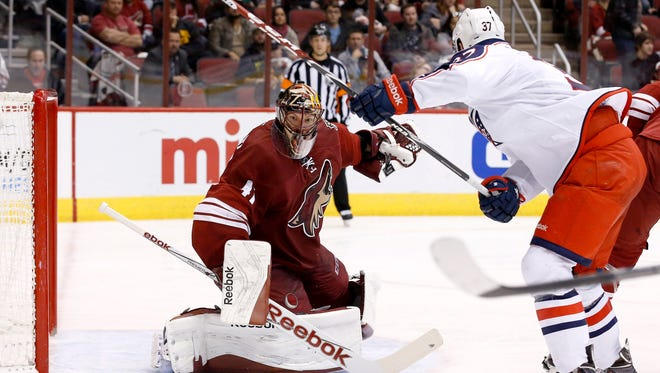 Arizona Coyotes' Mike Smith (41) makes a save on a shot by Columbus Blue Jackets' Sean Collins (37) during the third period of an NHL hockey game Saturday, Jan. 3, 2015, in Glendale.