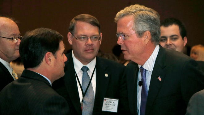 Former Florida Gov. Jeb Bush, right, talks with Republican Arizona Gov. Doug Ducey, left, after Bush delivered the keynote address at the Republican National Committee spring meeting Thursday, May 14, 2015, in Scottsdale, Ariz.  Bush has not yet announced his intention to join the field of Republican presidential candidates for the 2016 election. (AP Photo/Ross D. Franklin)