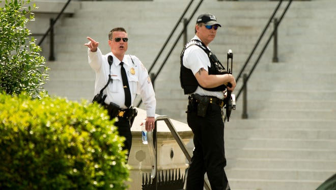 A uniformed Secret Service officer orders people into buildings near the entrance to the West Wing of the White House in Washington Friday, after the White House was placed on security alert after shooting on street outside.