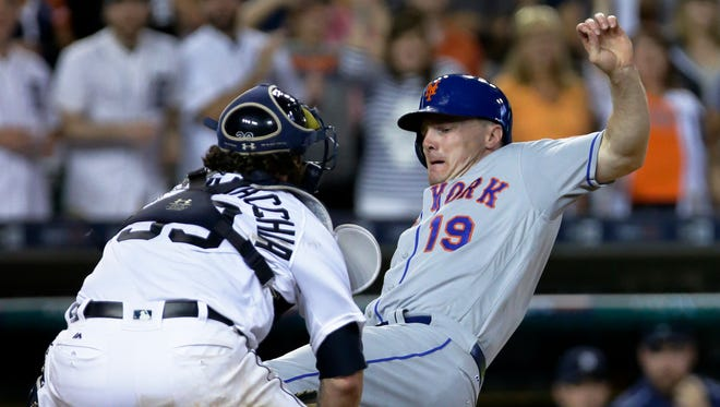 New York Mets' Jay Bruce (19) slides into the tag from Detroit Tigers catcher Jarrod Saltalamacchia while trying to score from second base during the ninth inning of an interleague baseball game Saturday, Aug. 6, 2016, in Detroit. The Tigers defeated the Mets 6-5.