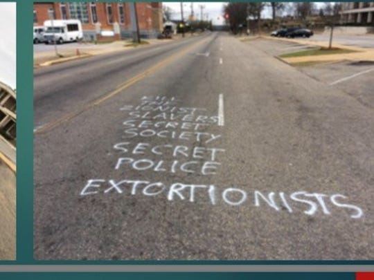 A suspect is in custody after spray painted terrorist threats were found outside the MPD headquarters and two other locations.