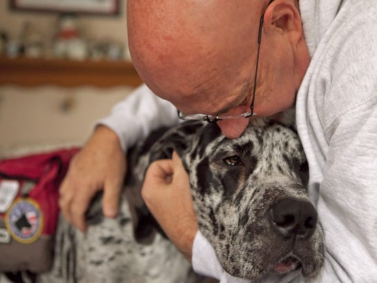 Bill Austin hugs his service dog JP, in this 2011 photo.