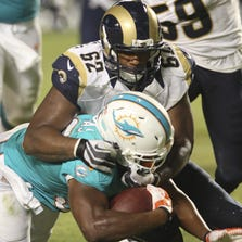 Daniel Thomas #33 of the Miami Dolphins is tackled by Ethan Westbrooks #62 of the St. Louis Rams in the second half at Sun Life Stadium on August 28, 2014 in Miami Gardens, Florida.