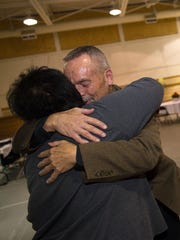 Central Consolidated School District board secretary Christina Aspaas hugs board member Randy Manning during a celebration of his service on the board on Tuesday in the Shiprock A-Gym in the CCSD administration building.