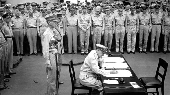 Gen. Douglas MacArthur signs the Japanese surrender documents, September 2, 1945, aboard the USS Missouri in Tokyo Bay. Standing  behind him are Lt. Gen. Jonathan Wainwright, left foreground, who surrendered Bataan to the Japanese, and British Lt. Gen. A. E. Percival, next to Wainwright, who surrendered Singapore, as they witness with other American and British officers the ceremony marking the end of World War II.