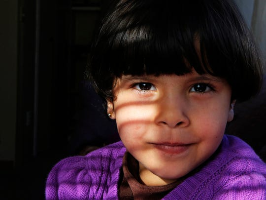 Rimas Marie Alhamoud, 4, poses for a portrait in her home. After her family escaped Homs, Syria, the city was destroyed.