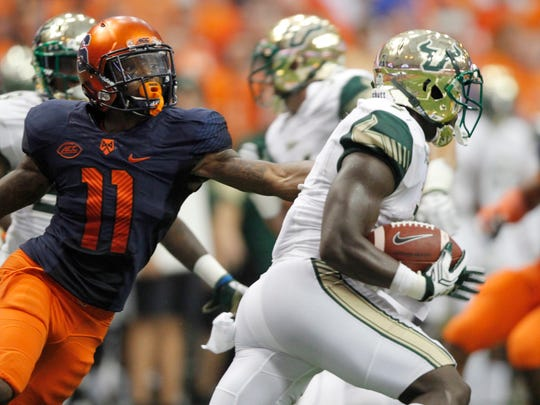 South Florida's D'Ernest Johnson, right, gets past Syracuse's Corey Winfield, left, and runs a kickoff in for a touchdown in the second half of an NCAA college football game in Syracuse, N.Y., Saturday, Sept. 17, 2016.